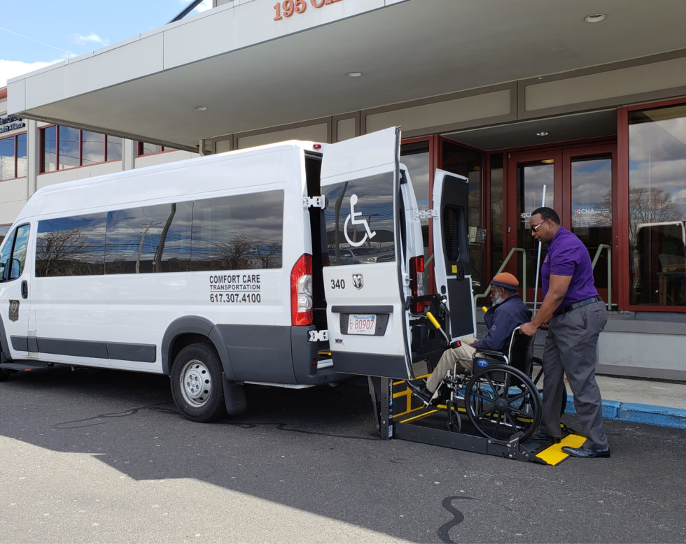 man helping an elderly man on a wheelchair get in the van